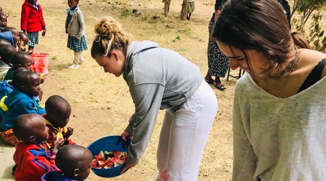 Two Projects Abroad volunteers provide a nutritious snack to Tanzanian children in Arusha